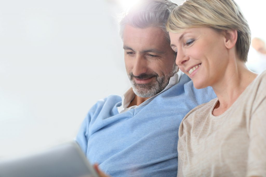 Middle-aged couple websurfing on internet with touchpad